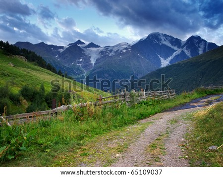 Road and fence on background of the mountains and green meadow. Natural composition - stock photo