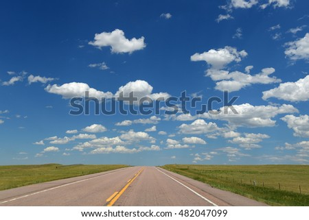 Road and landscape with clouds and blue skies