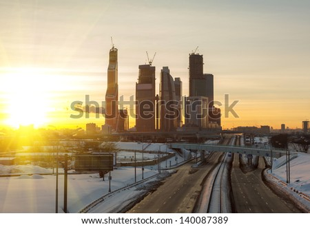 road and skyscrapers of Moscow against the sky and sunrise