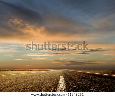Road and the sunset sky - stock photo