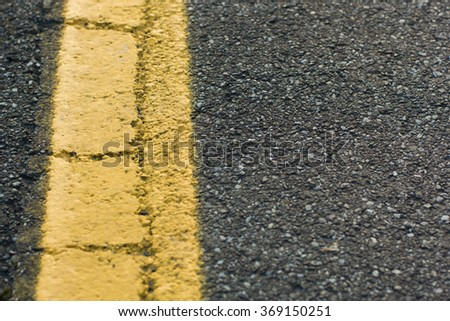 road asphalt with stripe painted in yellow with cracks and horizontal composition