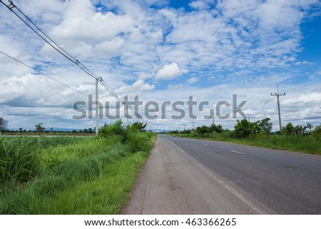 Road at countryside with electricity post with blue sky