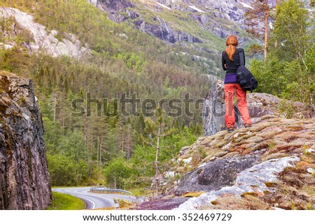road at the norwegian mountains and  girl  hiker with a backpack standing on a rock, Norway - stock photo