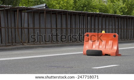 Road barrier block placed in the center of the road warning about a damage in pavement - stock photo