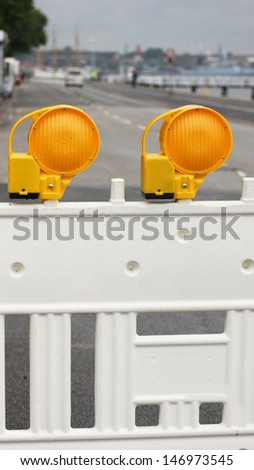 road barrier with two yellow warning lights  - stock photo