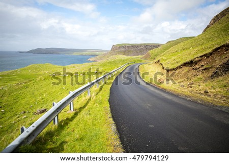 Road bending to the right side with view of the ocean and cliffs