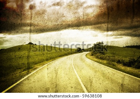 Road between fields under a cloudy sky - stock photo