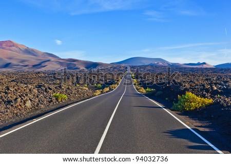 Road between rocks  in Timanfaya national Park - stock photo