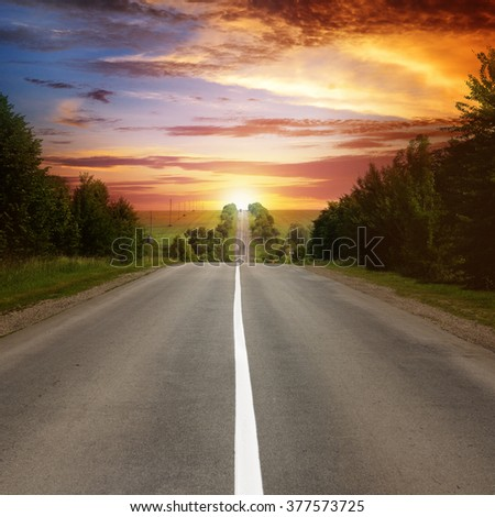 road between trees and beautiful sunset - stock photo