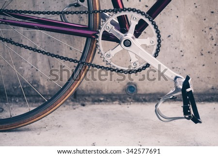 Road bicycle, fixed gear bike on city concrete street. Urban industrial cycling, bike chain on city scene bicycle closeup details, vintage old retro bike, cycling industrial concept. - stock photo