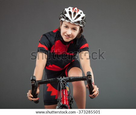 Road bicycle woman riding her bike and concentrating on winning the cycle race. full cycle gear and action as a real cyclist trains for fitness.  - stock photo