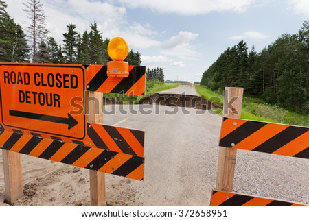 Road closed detour sign on blocked washed out road with rain flood washout damaged broken asphalt