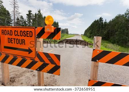 Road closed detour sign on blocked washed out road with rain flood washout damaged broken asphalt - stock photo