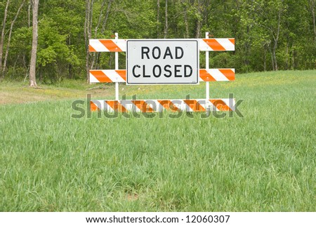 Road closed sign in field - stock photo