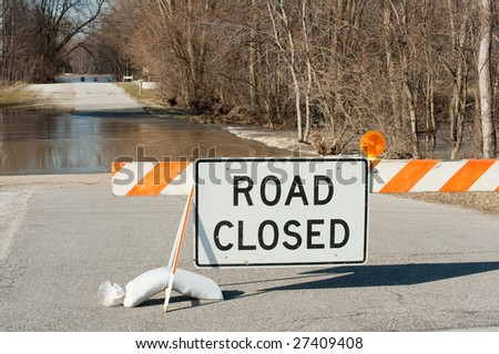 Road closed sign with flooded road and the Maumee river in the background. - stock photo