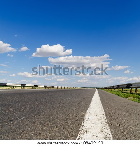 road closeup under blue sky - stock photo