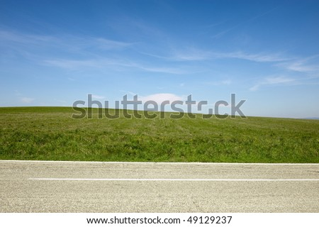 Road, cloudy sky and grass - stock photo