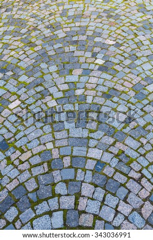 Road cobbled by a granite stone blocks overgrown with moss - stock photo
