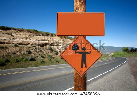 Road construction and flagger sign screwed on wooden pole against winding road - stock photo