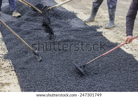 Road construction crew used shovels to scatter more asphalt over the top of the new pavement. At road construction site. Selective focus.  - stock photo