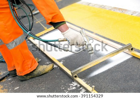 Road construction painter worker painting zebra crossing sign on city street surface during road traffic markings or renovation works with spray gun tool - stock photo