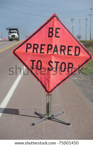 "Road construction sign ""Be Prepared to Stop"" with truck approaching, selective focus on sign - stock photo"