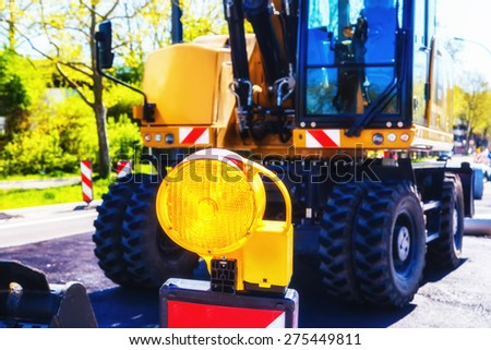 Road construction site in city with excavator and yellow flash signal - stock photo