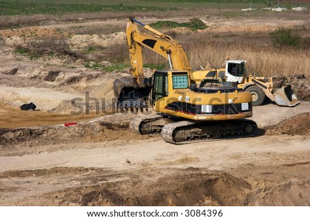 Road construction site with yellow excavator doing soilwork