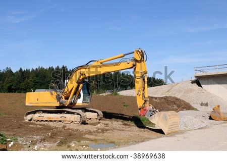 Road construction with yellow excavator