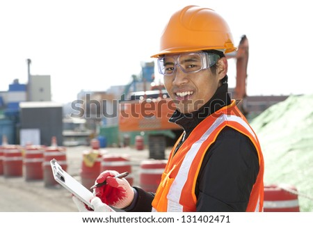 road construction worker  holding a  clipboard on the excavator background - stock photo
