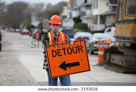 Road construction worker holding a detour sign and gesturing to stop.