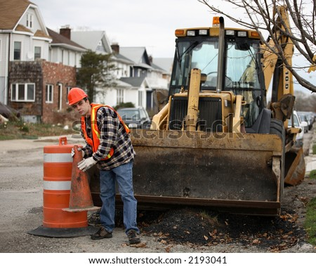 Road construction worker holding orange cone in front of an bulldozer. Residential area on the background. - stock photo