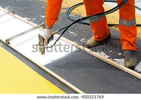Road construction worker painting zebra crossing sign on city street surface during asphalt concrete pavement renovation works with spray gun tool - stock photo