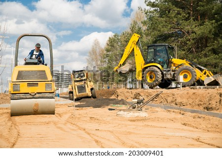 Road construction works with commercial equipment - stock photo