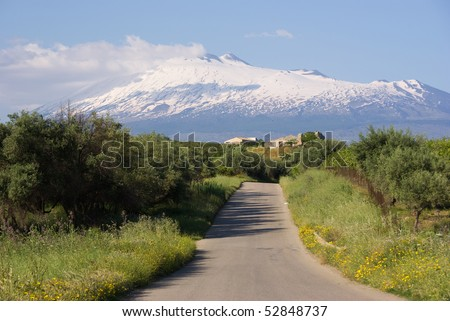 road crosses a rural area is pointing toward mount Etna - stock photo