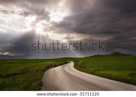 road crosses prairie covered by clouds into rays of sun - stock photo