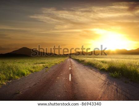 road crosses rural landscape with the silhouette of hill on background the colors of a fiery sunset - stock photo