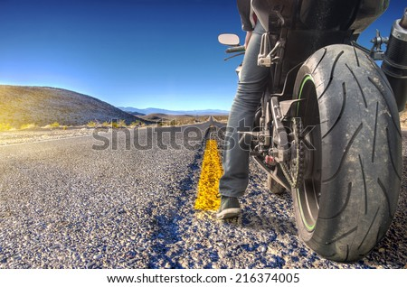 Road crossing the Death Valley, motorbike ready to ride - stock photo
