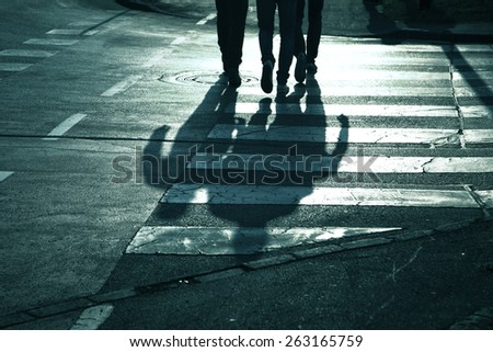 Road crossing with pedestrians feet. Blue color tone added. - stock photo