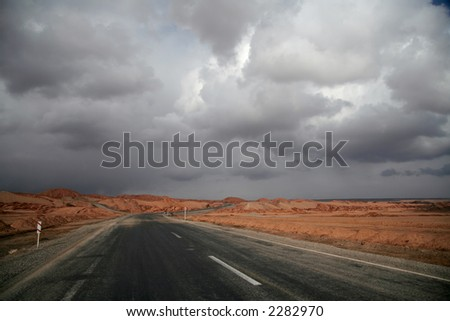 Road cutting through a Big Salt Desert in the middle of Iran. - stock photo