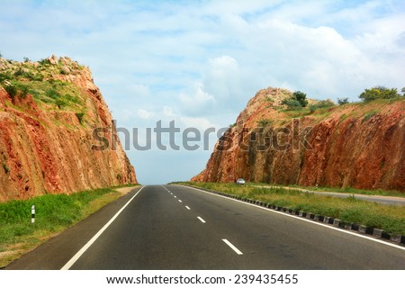 Road cutting through the hill. - stock photo