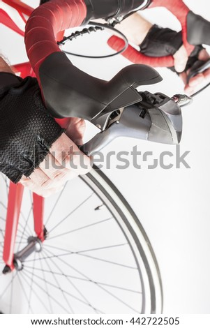 Road Cycling Sport Ideas and Concepts. Closeup of Athlete Hands in Gloves Holding Dual Controls Levers. Vertical Image - stock photo