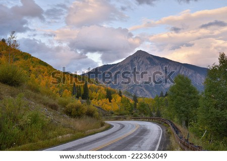 road descending into crested butte colorado on an autumn twilight evening - stock photo