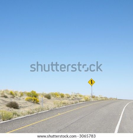 Road disappearing into horizon with merge road sign. - stock photo