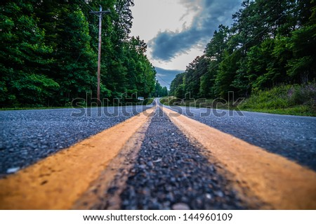 road double lane perspective with treeline and clouds - stock photo
