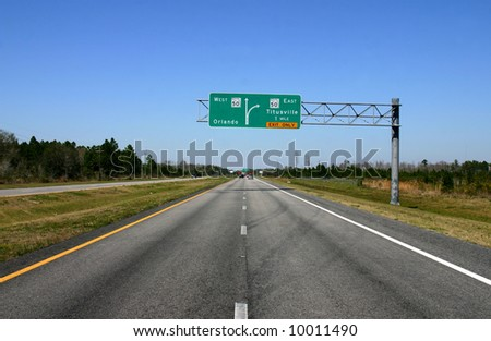 Road fading into Distance with Road sign giving directions in mid-ground - stock photo