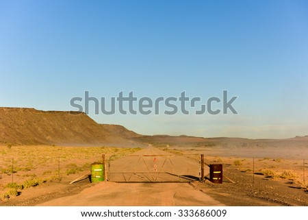 Road fence to hold wildlife in the Fish River Canyon in Namibia, Africa. It is the largest canyon in Africa. - stock photo