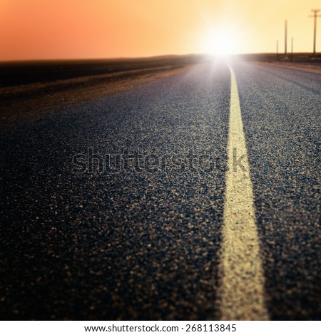 Road heading the sun - stock photo