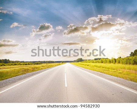 road in a fields at sunset - stock photo