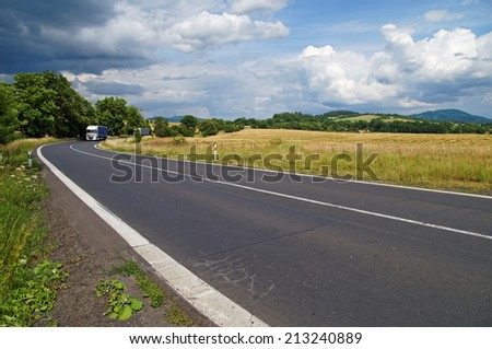 Road in a rural landscape with dramatic clouds in the sky, two trucks leave from the trees bend, in the background cornfield and wooded mountains - stock photo